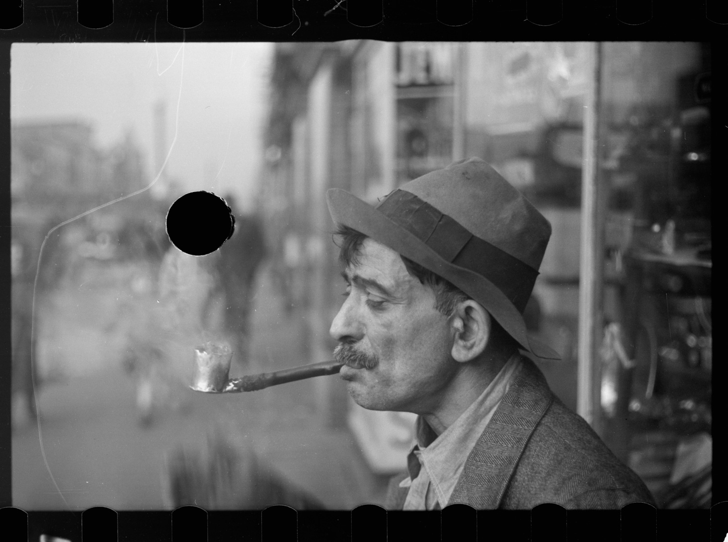 Photograph of a white man smoking a pipe. A hole is punched in the blurry background, through the heads of a walking couple.