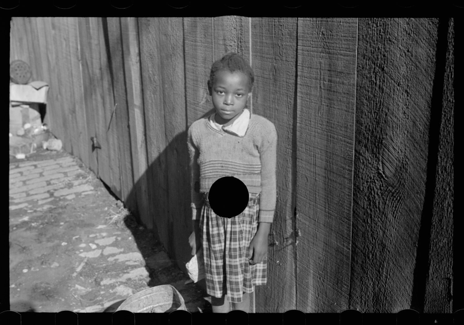Photo of a young black girl with a hole punched through the center of her stomach