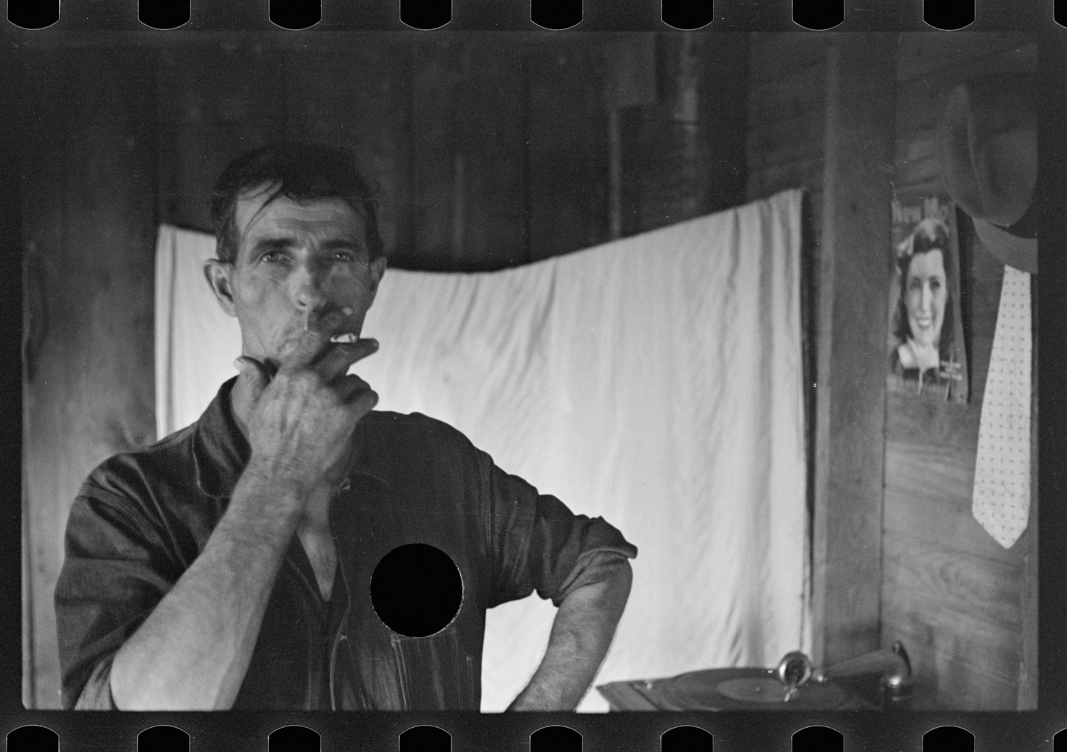 Photograph of a white man smoking a cigarette with a whole punched through his shirt. In the background are wooden walls, a hung sheet, and a phonograph.